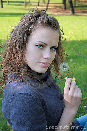 Beautiful girl holds a dandelion in a hand