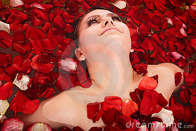 Beautiful girl in jacuzzi with rose petal.