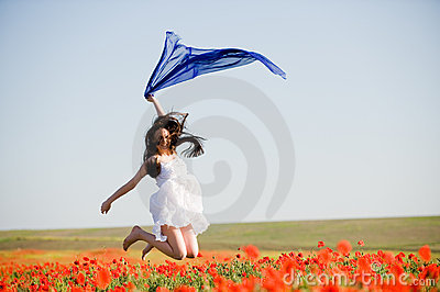 Beautiful girl jumping in the poppy field