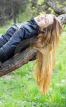 Beautiful girl laughing, on a tree branch