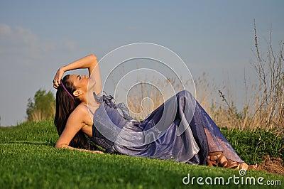 Beautiful girl laying on a grass