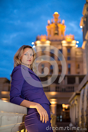 Beautiful girl is leaning on the parapet