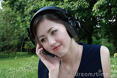 Beautiful girl listening music in the park