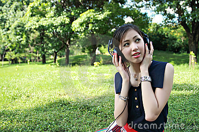 A beautiful girl listening to music in the park