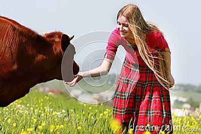 Beautiful girl with long hair feeding cow