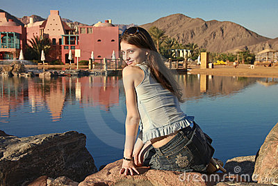 Beautiful girl with long hair is sitting on stone