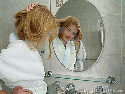 The beautiful girl looks in a mirror in a bathroom