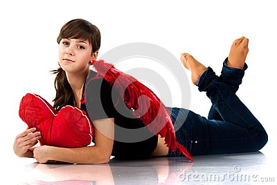 Beautiful girl lying with heart shaped red pillow