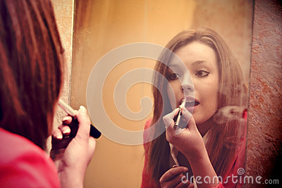 Beautiful girl make up in front of the mirror