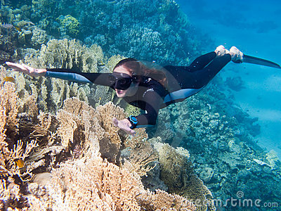 Beautiful girl with monofin swims above corals