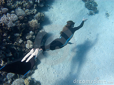 Beautiful girl with monofin swims near coral reef