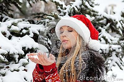 Beautiful girl near Christmas tree with snow