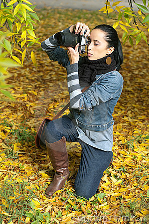 Beautiful girl photographer knee on nature