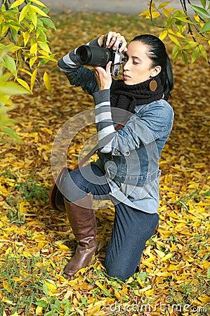 Beautiful girl photographer knee on nature