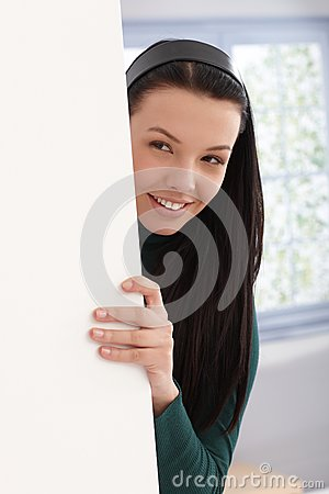 Beautiful girl playing peek-a-boo behind wall