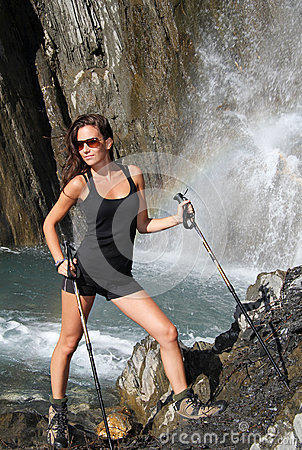 Beautiful girl poses under mountain waterfall