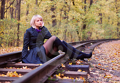 Beautiful girl posing on rails in autumn park