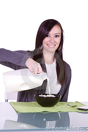 Beautiful Girl Pouring Milk to her Cereal