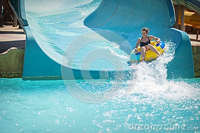 Beautiful girl pulls off the slides at the water park