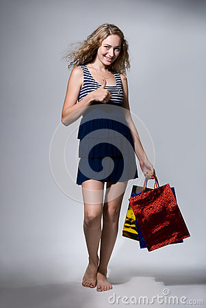 Beautiful girl with purchases shows a thumb