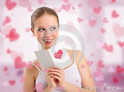 Beautiful girl reads  a postcard valentine