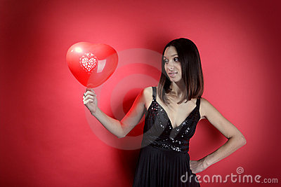 Beautiful girl with a red balloon in the form of h