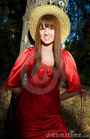 Beautiful girl in a red dress and a straw hat