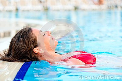 Beautiful girl relaxes in the pool