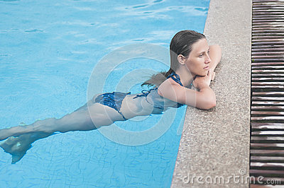 Beautiful girl resting in swiming pool