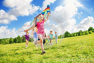 Beautiful girl run with kite together with friends