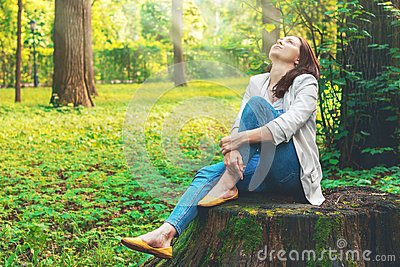Cute woman is enjoying of picturesque nature. Camping, rest. Beautiful girl sits on a big old stump in the forest. Stock Photo
