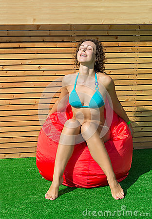 Beautiful girl sits on a soft red pufe