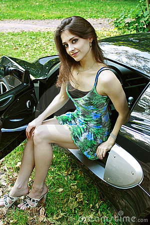 The beautiful girl is sitting in the car
