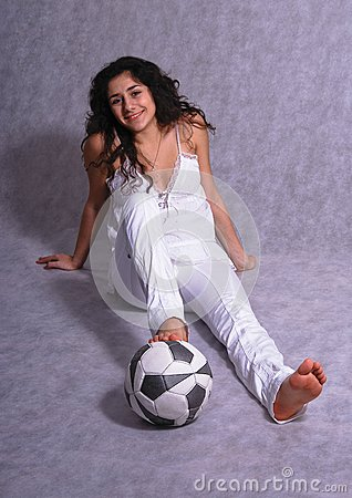 Beautiful girl sitting on a floor with a ball