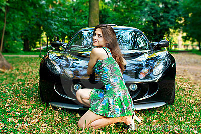 Beautiful girl is sitting in front of sport car