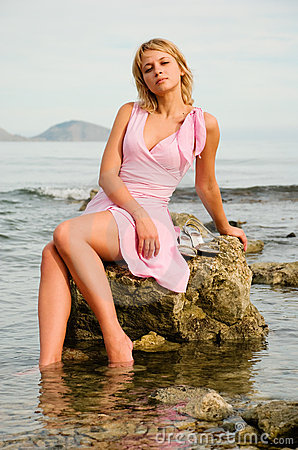Beautiful girl sitting on a rock at the beach