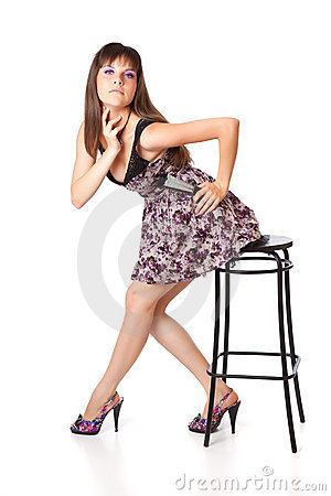Beautiful girl is sitting on a stool