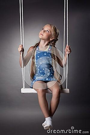 Beautiful girl sitting on swing
