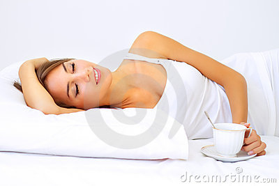 Beautiful girl sleeping with a cup of coffee