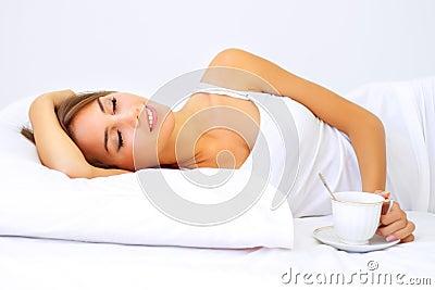 Beautiful girl sleeping with a cup of coffee
