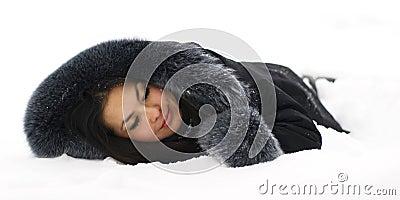 Beautiful girl sleeping in the snow