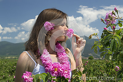 Beautiful girl smelling a rose in a rose field
