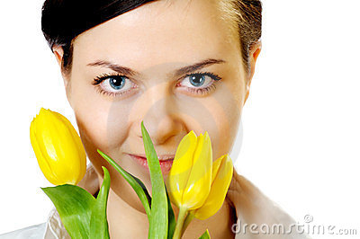 Beautiful girl smells yellow tulips