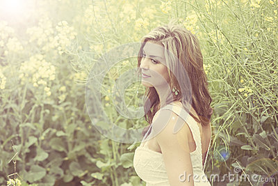 A beautiful girl smiling in a field of yellow flowers