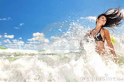 Beautiful girl splashing in the ocean