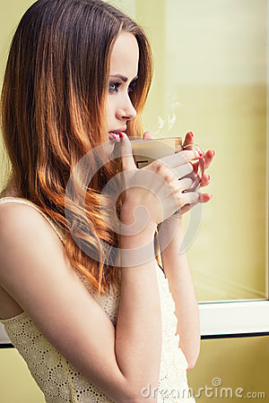 Free Beautiful Girl Standing At The Window With A Hot Cup Of Invigorating Coffee Early In The Morning Stock Image - 46809531