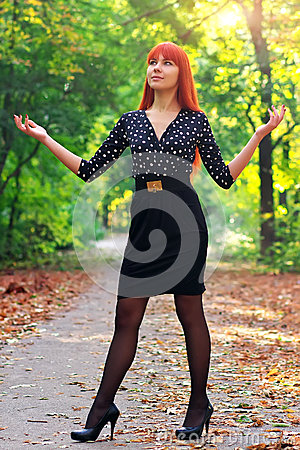 Beautiful girl standing in a park in autumn.