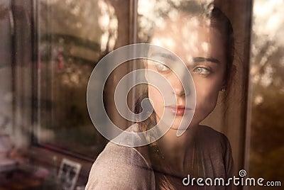 Beautiful girl standing at the window watching