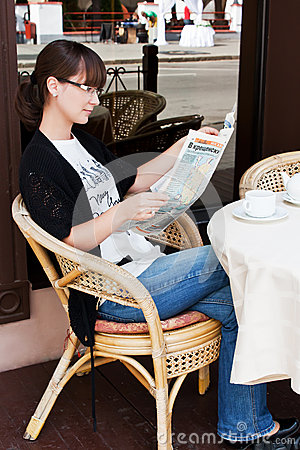 Beautiful girl in a summer cafe reading newspaper