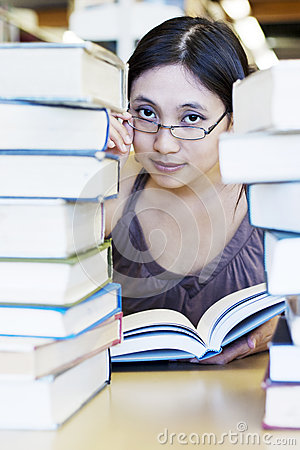 Beautiful girl surrounded by library books